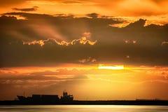 Frachtschiff schwimmt auf den Ozean zur Sonnenuntergangzeit Lizenzfreie Stockfotos
