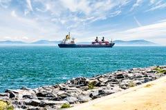 Frachtschiff segelt auf einen Hintergrund von blauen Bergen Lizenzfreie Stockbilder