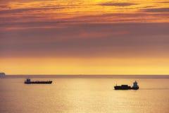 Frachtschiff und Erdöltanker bei Sonnenuntergang Stockbild