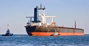 Frachtschiff und zwei Schlepper. Lizenzfreie Stockfotos