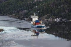 Frachtschiff, welches das ringdalsfjord verlässt Stockfotografie