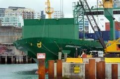 Frachtschiffarbeitskräfte, die Behälter in den Häfen von Auckland entladen Stockbilder