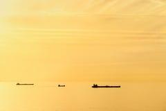 Frachtschiffe bei Sonnenuntergang mit ruhigem See Lizenzfreies Stockfoto