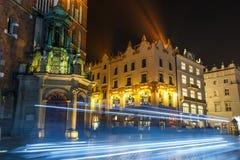 Frachtu światło wlec przed Mariacki kościół na Głównym Targowym kwadracie w Krakow, noc rywalizuje Obrazy Stock