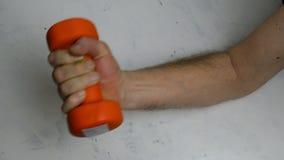 Fraco, sem o braço masculino dos músculos faz um exercício com um peso alaranjado filme