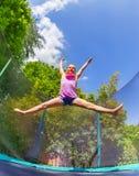 Fractura del acróbata de la muchacha que salta en el trampolín al aire libre fotografía de archivo libre de regalías