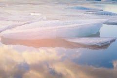 Fractura del hielo en el lago con la reflexión del cielo fotos de archivo