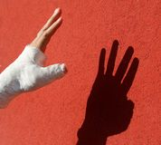 Fractured and cast hand and the shadow on the red wall royalty free stock photography