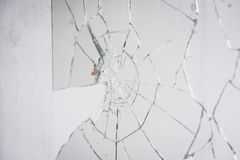 Fractured mirror on wall. Close-up of broken mirror on wall royalty free stock photography