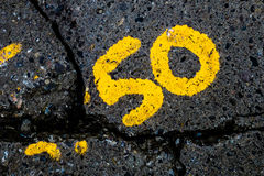 So fractured at 50. Yellow number 50 on a cracked sidewalk Stock Photo