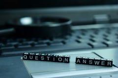 Frage-Antworttextholzklötze im Laptophintergrund Geschäfts- und Technologiekonzept lizenzfreies stockbild