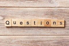 Fragen fassen geschrieben auf hölzernen Block ab Fragentext auf Tabelle, Konzept Stockbild