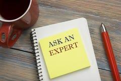Fragen Sie einen Experten Notizblock mit Mitteilung, rotem Bleistift und Kaffeetasse Büroartikel auf Schreibtischtischplatteansic Stockfotografie