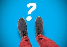 Fragezeichen und graue Schuhe auf Füßen mit blauem Hintergrund Stockbild