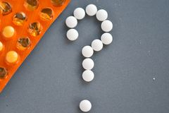 Fragezeichen von den Pillen mit der orange Drogenblase Lizenzfreie Stockfotos