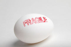 Fragile. A white egg stamped with the word FRAGILE stock image