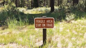 Fragile Area Sign. Brown fragile area stay on trail sign on a trail royalty free stock photo