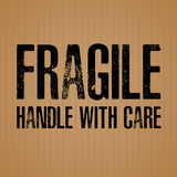 Fragile Black text on brown cardboard texture background. Royalty Free Stock Images