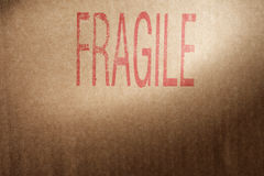 Fragile Contents. Closeup of a brown cardboard box with word Fragile stamped with red ink royalty free stock photos