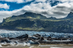Fragile Environment. Melting Glacier with glacial lake in front of a green mountain Stock Photos