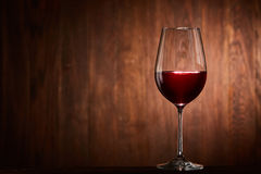 Fragile goblet of the red wine on the wooden stand on wooden wall background. Stock Photo
