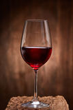 Fragile goblet of the red wine on the wooden stand on wooden wall background. Stock Photography