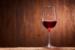 Fragile goblet of the red wine on the wooden stand on wooden wall background. Royalty Free Stock Image