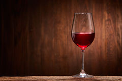 Fragile goblet of the red wine on the wooden stand on wooden wall background. Royalty Free Stock Photography