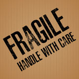 Fragile with Handle with care on brown cardboard texture background. Stock Image