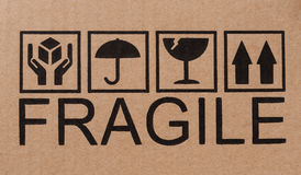 Fragile icons on cardboard Stock Photos