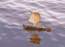 Tree bark boat alone on the sea in sunset.