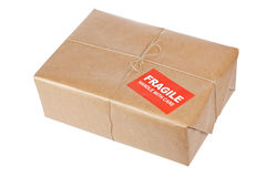 Fragile package. A fragile parcel wrapped in brown paper and tied with rough twine, isolated on white background. Shallow depth of field and path included royalty free stock photography