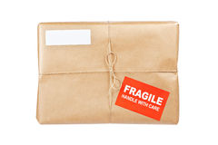 Fragile package. A fragile parcel wrapped in brown paper and tied with rough twine, isolated on white background. Shallow depth of field royalty free stock photography