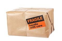 Fragile package. A fragile parcel wrapped in brown paper and tied with rough twine, isolated on white background. Shallow depth of field royalty free stock photo