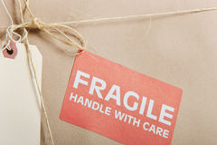 Fragile Package. Wrapped in brown craft paper with label; tag and string on it Stock Photography