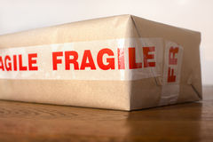 Fragile parcel. A parcel wrapped in brown paper and marked fragile Stock Photo