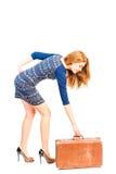 Fragile slender girl lifts heavy suitcase Stock Photo