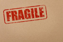 Fragile stamp. Fragile text on a cardboard package with copy space stock photos