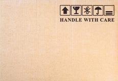 Fragile symbol on cardboard background. Inscription `handle with care` and fragile symbol on cardboard background stock photo