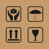 Fragile symbol on cardboard. Set of fragile icons on cardboard. Umbrella,glass, arrow and hands box signs Stock Photography
