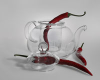 A fragile transparent glass teapot, a lid from a kettle with a large bowl lying side by side and three red hot peppers: one pepper Royalty Free Stock Photos