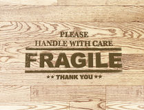 Fragile word stamp on wood plank background Royalty Free Stock Image