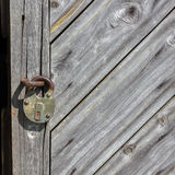 Fragment of aged boarded door with padlock. Stock Photos