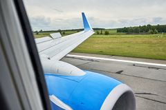 Fragment of the aircraft and the runway, the view from the cabin. The view from the illuminator of the landing aircraft on the engine and wing with raised flaps stock image