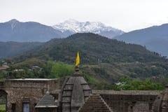Fragment alten Shiva-Tempels bei Baijnath, Himachal Pradesh, Indien mit grünen Hügeln und schneebedeckten Bergen im Hintergrund Lizenzfreie Stockfotografie