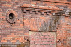 Fragment of ancient brick wall. Round hole ventilation and square arch over the window stock image