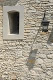 Fragment of the ancient castle with street lamp and a window. Window with a lattice in the stone wall of the old fortress stock photography