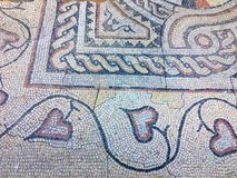 Fragment of an ancient floor mosaic. Colorful small tiles, unusual geometric ornament, floral and regular forms. Crimea stock photography