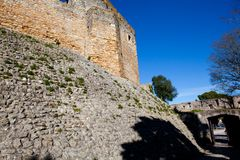 A fragment of an ancient fortress wall with blue sky in the back. Ground Stock Image