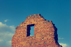 Fragment of ancient ruined building with window on blue sky Stock Photos
